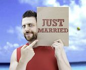 Man holding a card with the text Just Married on a beach background