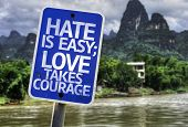 Hate is Easy Love Takes Courage sign with a forest background