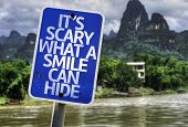 It's Scary What a Smile Can Hide sign with a forest background