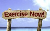 Exercise Now! sign with a beach on background