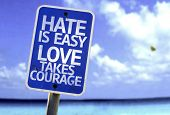Hate is Easy Love Takes Courage sign with a beach on background