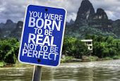 You Were Born To Be Real Not To Be Perfect sign with a forest background