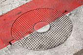 image of cross-hatch  - Closed round sewer manhole with stars pattern under red and white road marking - JPG