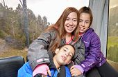 Portrait Of Three Siblings Hugging In A Cable Car