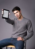 Handsome Young Man Holding And Showing Ebook Reader