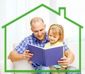 family, children, education, school and happy people concept - smiling father and daughter reading book at home behind green house symbol