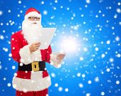 christmas, holidays and people concept - man in costume of santa claus reading letter over blue snowy background