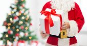 christmas, holidays and people concept - close up of santa claus with gift box over living room with tree