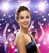 holidays, party and people concept - smiling woman in evening dress over disco background