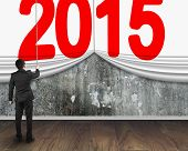 Businessman Pulling Down 2015 Curtain To Cover Mottled Concrete Wall