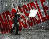 Businessman Holding Sledgehammer Hitting Red Impossible Word On Concrete Wall