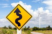 Winding Road Sign With Windmill Background In Wind Farm.