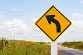 Left Curved Road Traffic Sign With Windmill Background And Clear Sky.