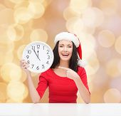 christmas, winter, holidays, time and people concept - smiling woman in santa helper hat and red dress with clock over beige lights background