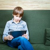 Portrait of 12 years boy wearing casual clothing using new touch pad at home