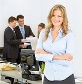 Portrait of an attractive female businesswoman with her colleagues in the background