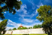 stock photo of old stone fence  - Blue sky with clouds framed by green trees old brick fence and church tower - JPG