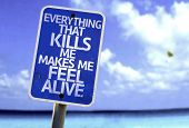 Everything That Kills Me Makes Me Feel Alive sign with a beach on background