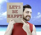 Man holding a card with the text Let's Be Happy on a beach background