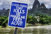 Everything That Kills Me Makes Me Feel Alive sign with a forest background