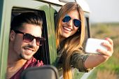 Portrait Of Pretty Couple Taking Selfie With Smartphone In The Car.