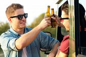Portrait Of Two Friends Toasting With Bottles Of Beer In Car.