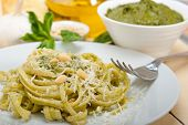stock photo of pine nut  - Italian traditional basil pesto pasta ingredients parmesan cheese pine nuts extra virgin olive oil garlic on a rustic table - JPG