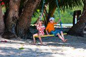 pic of tire swing  - Kids having fun on swing on summer day - JPG