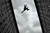 pic of roofs  - Man jumping over building roof against gray sky background  - JPG