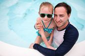 picture of swimming pool family  - Happy family father and his adorable little daughter at outdoors swimming pool - JPG