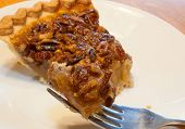 picture of pecan  - Big piece of pecan pie on a fork with more behind - JPG