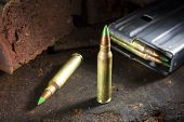stock photo of ammo  - Small rifle ammo with green tips and a loaded magazine behind - JPG