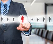 stock photo of recruiting  - Businessman pressing button on virtual screens - JPG