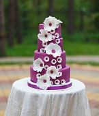 stock photo of violets  - Grand violet wedding cake with white sugar paste flowers - JPG