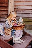 stock photo of country girl  - happy blonde child girl playing with easter decorations at country house in spring - JPG