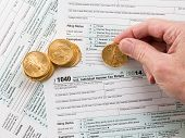 stock photo of irs  - Caucasian hand counting solid gold eagle coins on USA tax form 1040 for year 2014 illustrating payment of taxes to the IRS - JPG
