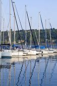 stock photo of boat  - Small sailing boats with tall masts mooring on Italian lake Garda in late summer afternoon - JPG