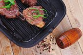 image of bloody  - roast bloody beef fillet steaks on black teflon grill plate on wood - JPG