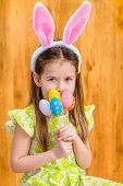 foto of rabbit year  - Portrait of smiling little girl with long blond hair wearing pink and white rabbit or bunny ears and holding bunch of painted colorful eggs - JPG