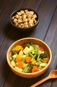 picture of vegetable soup  - Wooden bowl of vegetable soup made of zucchini green bean carrot broccoli potato and pumpkin with a small bowl of croutons in the back photographed on dark wood with natural light  - JPG