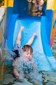 stock photo of inflatable slide  - big water splash in his face while sliding down - JPG