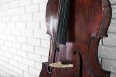stock photo of cello  - Cello on bricks wall background - JPG
