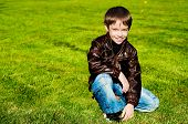 Little boy sitting Down on thegrass