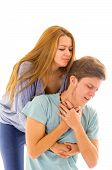 image of choke  - Couple demonstrating first aid procedure for abdominal thrusts, Heimlich Manoeuvre or Maneuver to treat man choking by foreign objects