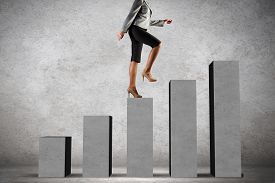 stock photo of step-up  - Young businesswoman stepping up on chart bar - JPG