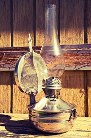 stock photo of kerosene lamp  - old kerosene lamp stands on wooden surface outdoors toning - JPG
