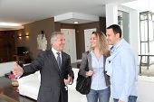 stock photo of real-estate agent  - Real estate agent showing modern house to couple - JPG