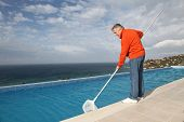 Senior couple cleaning swimming pool