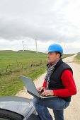 Engineer working on laptop computer in wind turbines field