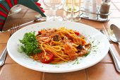 Spaghetti with a tomato sauce on a table in cafe